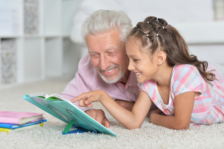 Grandfather helping his granddaughter to do homework