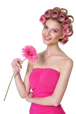 Schöne Frau mit Lockenwicklern mit Blume auf weißem Hintergrund
