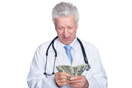Portrait of senior male doctor posing against white background with money Stock fotó