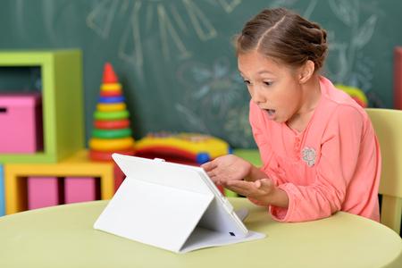 Portrait of cute little girl using tablet
