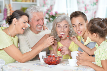 Portrait of big happy family eating fresh strawberries