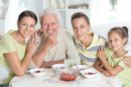 Portrait of happy family eating fresh strawberries 写真素材