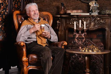 Portrait of senior man drinking at home