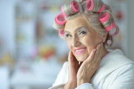 Porträt einer älteren Frau im Bademantel mit Lockenwicklern