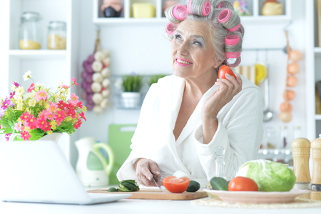 Senior woman in hair rollers cutting vegetables on kitchen
