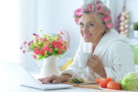 Portrait of senior woman in bathrobe with curlers sitting at table with laptop
