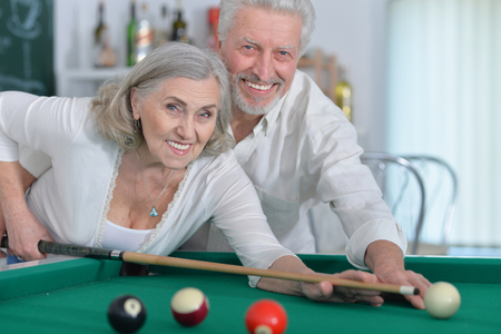 Close up portrait of senior couple playing billiard