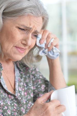 Close up portrait of stressed senior woman crying