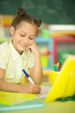 Portrait of a cute girl doing homework 免版税图像