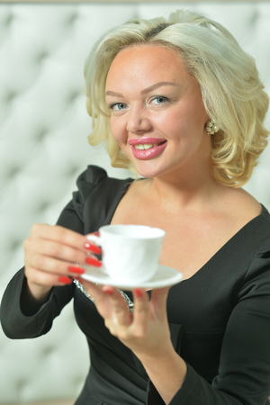 Portrait of a cute young woman drinking coffee