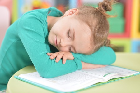 Portrait of a cute tired schoolgirl sleeping after studying Stock fotó