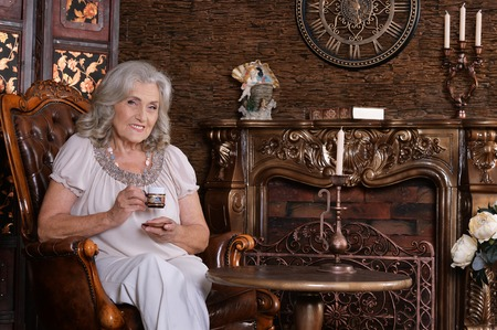 Portrait of senior woman with coffee in chair Banque d'images - 113988041