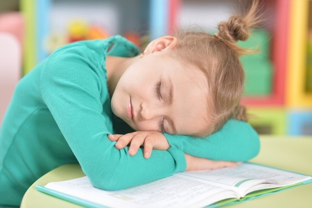 Portrait of cute tired schoolgirl sleeping after studying