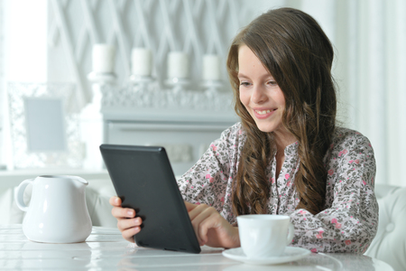 Close-up portrait of cute girl using tablet while drinking tea at light kitchen Stock Photo