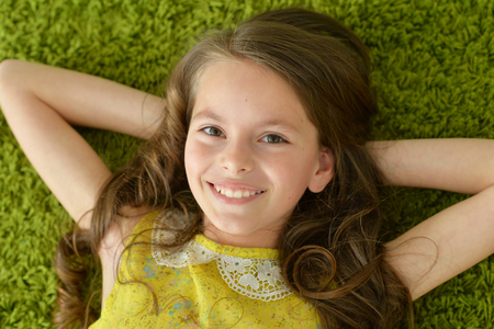 Close-up portrait of funny smiling little girl lying on green carpet