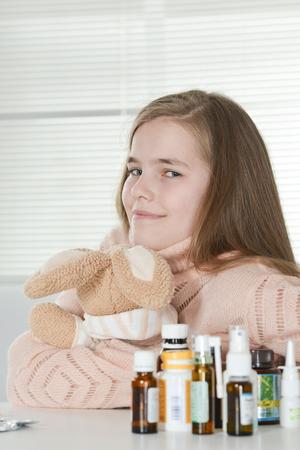 Close-up portrait of cute little girl taking medicine