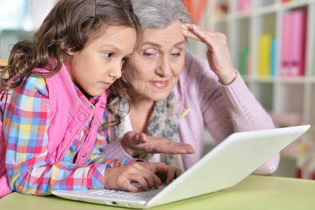 portrait of grandmother and daughter using laptop