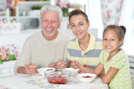 Portrait of a grandfather and grandchildren eating fresh strawberries