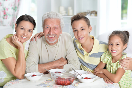 Portrait of a happy family eating fresh strawberries Stock Photo