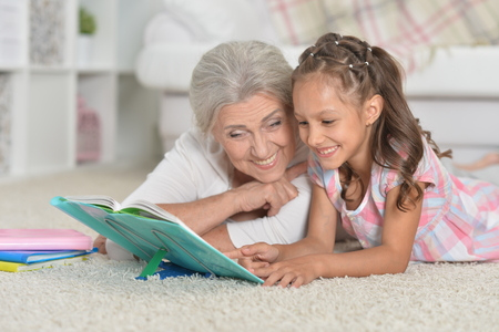 Grandmother with cute little girl doing homework together while Stock Photo