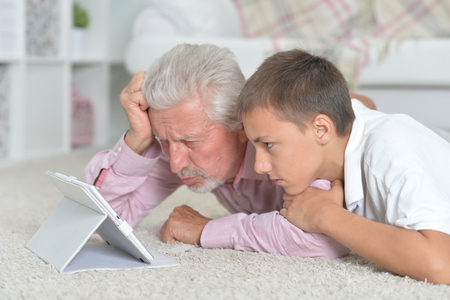 Grandfather with grandson using tablet while lying on floor Stock Photo