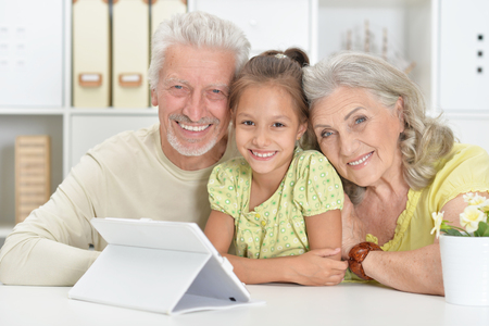 Grandparents with her granddaughter using tablet together