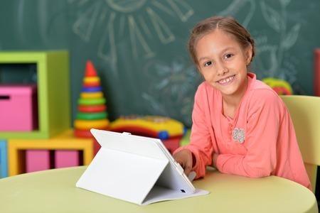Portrait of a little girl using tablet Фото со стока