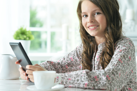 Portrait of cute girl using tablet while drinking tea at light kitchen Stock Photo