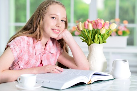 Cute schoolgirl sitting at table  and reading
