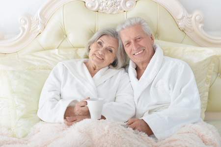 Senior couple in bed with tea Stock Photo