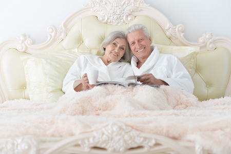 Portrait of senior couple in bed with tea