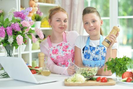 Two funny girls preparing fresh salad Banco de Imagens