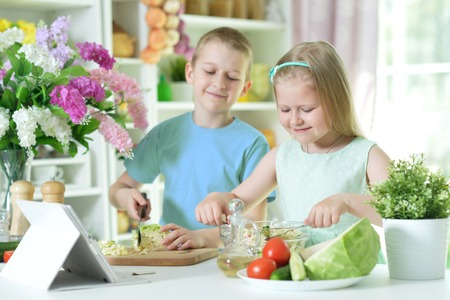 Cute little brother and sister cutting vegetables Foto de archivo