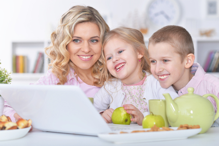 happy mother and children sitting at table Stock Photo