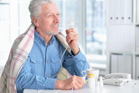 Portrait of smiling sick senior man with inhaler Imagens
