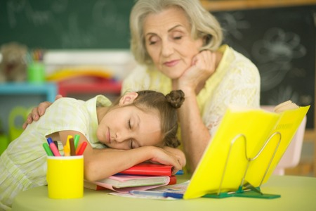 Grandmother with little girl doing homework together Stok Fotoğraf