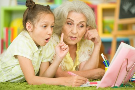 Grandmother with little girl doing homework Stok Fotoğraf