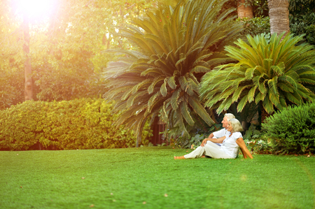 Portrait of happy senior couple sitting on green meadow