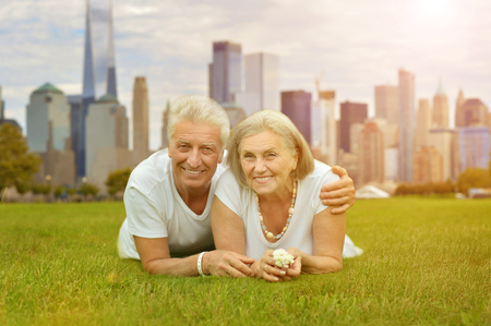 happy senior couple posing on green meadow against