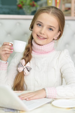 cute happy girl with cup using laptop