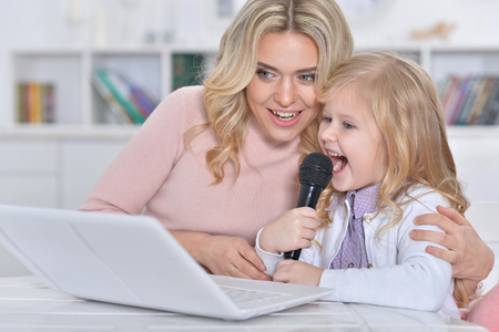 Portrait of young woman with girl using laptop and singing karaoke Imagens