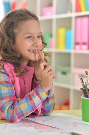 Portrait of little girl drawing at her room