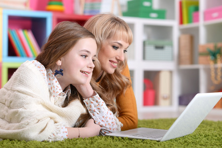 Portrait of young woman with girl using laptop Stock Photo