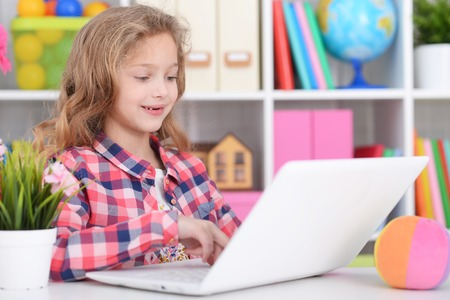 Little girl in checkered shirt using modern laptop Фото со стока - 116392032