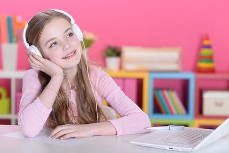 Portrait of cute girl in headphones using laptop
