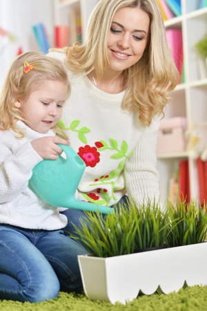 little girl with mother watering house plants