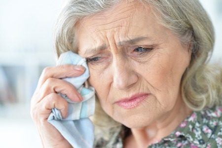 close-up portrait of stressed senior woman crying Stock Photo