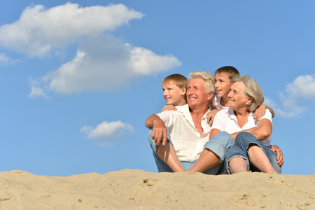 Grandparents with their grandchildren on the sand 写真素材