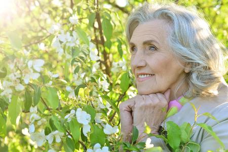 Portrait of smiling elderly woman posing in summer park