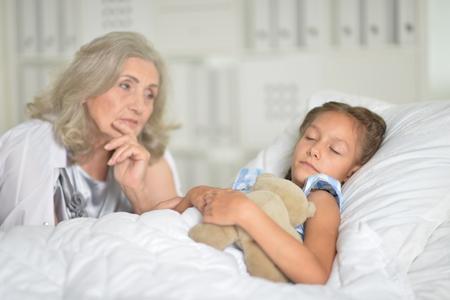 Portrait of sad senior woman with granddaughter 스톡 콘텐츠